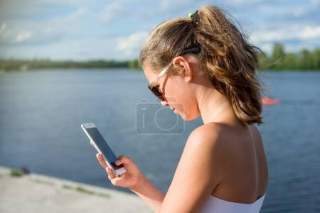 Photo for Young cute teen girl reading sms on her smartphone, view from behind. Against the background of the river in the city. - Royalty Free Image