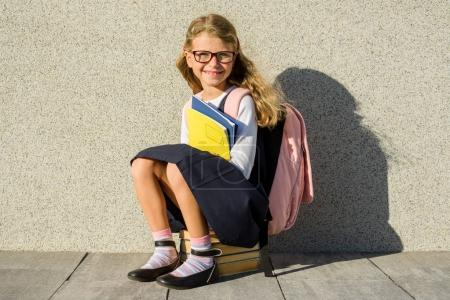 Photo for A pupil of elementary school with notebooks in his hand. Girl with a backpack near the building outdoors. Start of classes. - Royalty Free Image