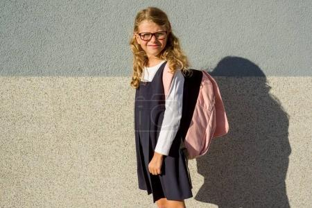 Photo for Outdoor portrait of an elementary school student in uniform with schoolbag. - Royalty Free Image