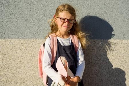 Photo pour La petite écolière a emmené son jouet à l'école avec elle. École primaire - Début des cours - image libre de droit