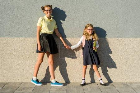 Photo pour Les sœurs mignon écolière en uniforme scolaire. Filles à lunettes, aller à l'école ensemble profitant à l'extérieur - image libre de droit