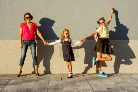 Photo for Mom and sister-teenager hold hands at schoolgirl elementary school. Starting school - Royalty Free Image