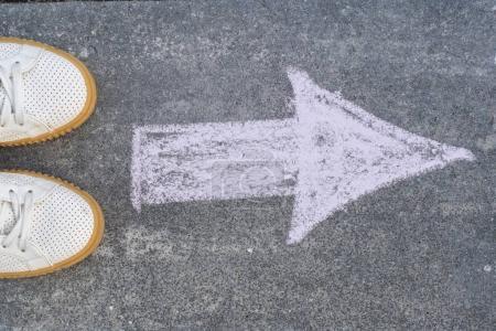 Photo pour Pieds et flèche sur route. Le symbole est dessiné à la craie. - image libre de droit