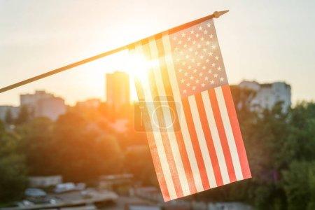 Photo pour Drapeau américain depuis la fenêtre sur fond de coucher de soleil - image libre de droit