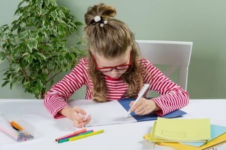 Photo pour Une écolière junior avec verres écrit quelque chose avec sa main gauche dans le bloc-notes et est assis à la table. Retour au concept de l'école. L'enfant est gaucher. - image libre de droit
