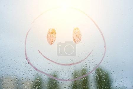 Positive funny smiley on a rainy autumn window