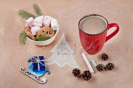 Photo pour Fond de vacances Noël avec boîte-cadeau sur le traîneau, tasse à café, biscuits, cônes, guimauve, arbre de Noël. Fond de papier Kraft, vue d'en haut. - image libre de droit