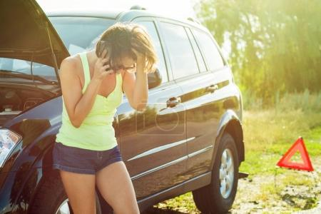 Photo for Woman with a black car that broke down on the road. Making telephone call to get help with the broken car. - Royalty Free Image