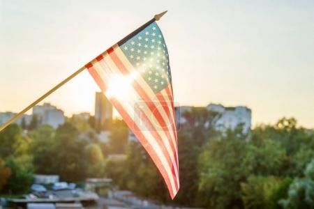 Photo pour Drapeau américain de la fenêtre sur fond de coucher de soleil - image libre de droit
