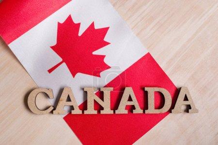 Photo pour Drapeau du Canada, le mot Canada en bois abstrait lettres, fond en bois - image libre de droit