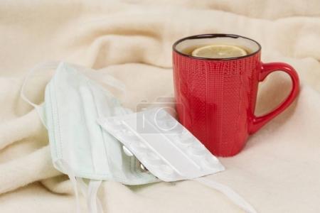 Photo pour Saison grippale - thé, masque médical, pilules, fond - fauteuil à carreaux - image libre de droit