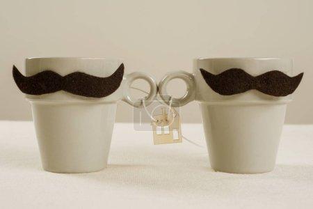 Photo pour Le concept de logement commun, une nouvelle maison, une famille. Les tasses symbolique du couple homosexuel, image en bois d'une maison. - image libre de droit