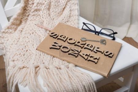 Photo pour Le livre est enveloppé dans du vieux papier et signé avec secrets de femme de lettres en bois, sur la clé du livre. Fauteuil fond blanc à l'intérieur de la maison. - image libre de droit