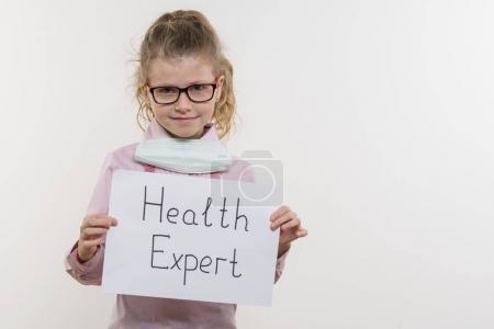 Photo pour Fillette tenant le morceau de papier avec un mot Expert en santé. Bakgrounde blanc, espace copie - image libre de droit
