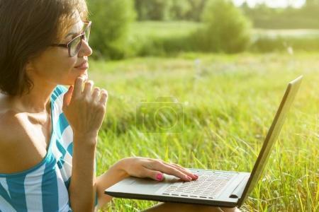 Photo pour Freelance, blogueuse portrait en plein air. Se penche sur le moniteur de l'ordinateur portable. - image libre de droit