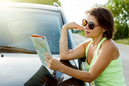 Photo for Cute female driver is traveling. Standing beside his car on a country road and watching a road map. - Royalty Free Image
