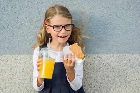Photo pour Mignonne blonde fille 7 ans manger un sandwich et boire du jus d'orange - image libre de droit