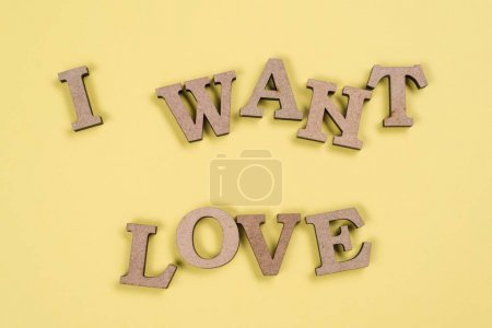 Photo for Word I want love in abstract wooden letters, yellow background. - Royalty Free Image