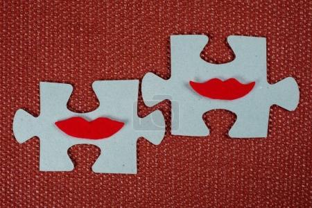 Photo pour Gros plan de deux parties d'un puzzle. Des femmes symboliques avec des lèvres. Le concept de compatibilité psychologique, d'amitié . - image libre de droit