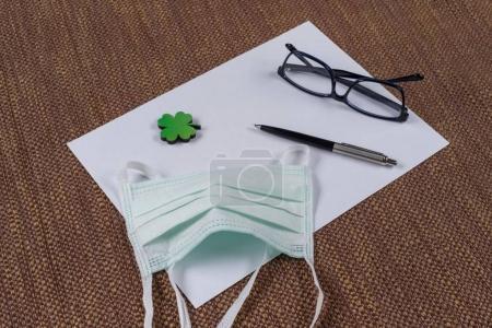 Foto de El concepto de ecología, protección de la naturaleza. Fondo - limpia papel, una hoja de trébol verde y una máscara de protección. - Imagen libre de derechos