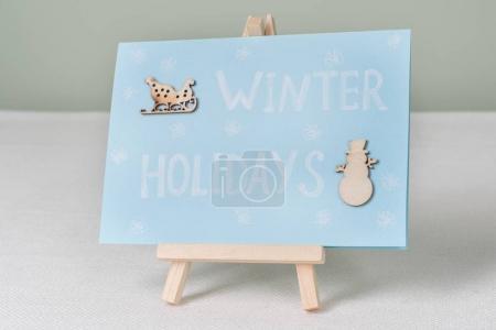 Foto de Vacaciones de invierno - una simbólica tarjeta de felicitación con un muñeco de nieve y trineos - Imagen libre de derechos