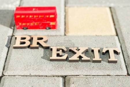 Photo pour Sortie de la Grande-Bretagne de l'Union européenne, Brexit terme abrégé en lettres vintage, fond double decker bus miniatures. - image libre de droit