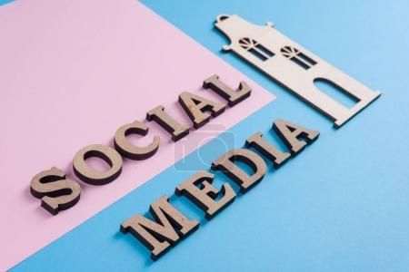 Photo for Text social media abstract wooden letters. Blue background with the image of house and pair of friends. People connecting and sharing social media - Royalty Free Image