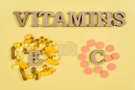 Photo for Vitamins And Supplements. Vitamin C, E. Background yellow, fish oil capsules and vitamin C vials - Royalty Free Image