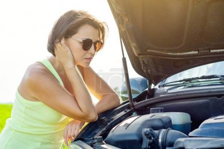 Photo for Frustrated woman driver near a broken car. Machine on a country road. The woman has stress - Royalty Free Image
