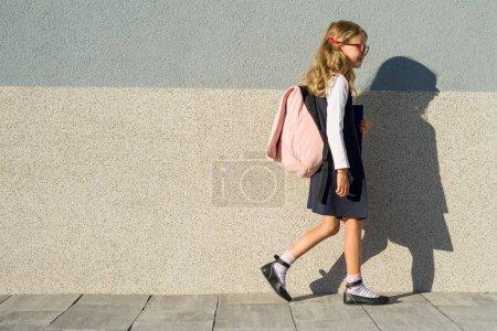Photo pour Une écolière de l'école primaire avec les ordinateurs portables à la main. Une fille avec un sac à dos va à l'école. Retour à l'école - image libre de droit