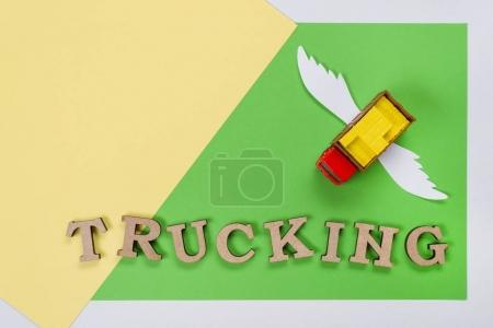 Photo for Abstract picture of a truck with wings and a word of trucking. Green background. Cargo transportation of the future - Royalty Free Image