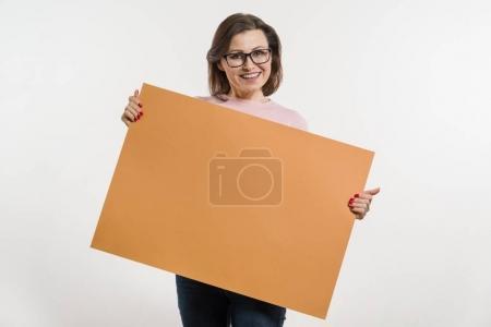 Photo pour Souriant le milieu femme âgée avec panneau d'affichage feuille orange, placard sur fond blanc - image libre de droit