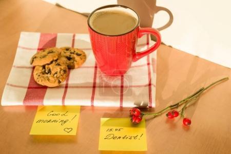 Foto de Buenos días etiqueta sobre la mesa en casa. Fondo - mantel con una taza de café y galletas - Imagen libre de derechos