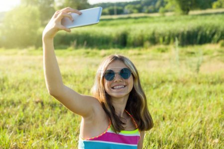 Photo for Young teenage girl using a smartphone doing selfie in the park. For your page in the instagram - Royalty Free Image