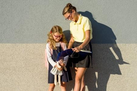 Photo for A high school student helps an elementary school student learn their homework. - Royalty Free Image