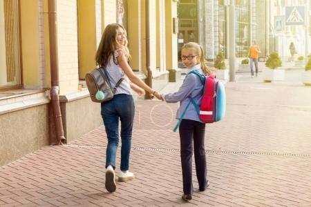Photo pour Vue arrière, élèves filles aller à l'école, tenant par la main. - image libre de droit
