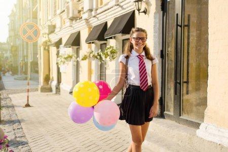 Photo pour Fille adolescente lycéen avec des ballons, à l'école en uniforme avec des lunettes va le long de la rue de la ville. Rentrée des classes. - image libre de droit