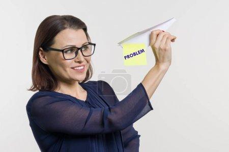 Photo pour Pas de problèmes. Une femme parle et laisse ses problèmes avec un avion en papier abstraite. - image libre de droit