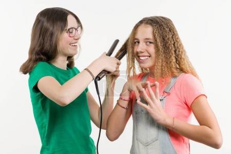 Photo pour Portrait de deux copines adolescentes faire coiffure à domicile. Fond blanc, les filles ont émotion, fer à lisser. - image libre de droit