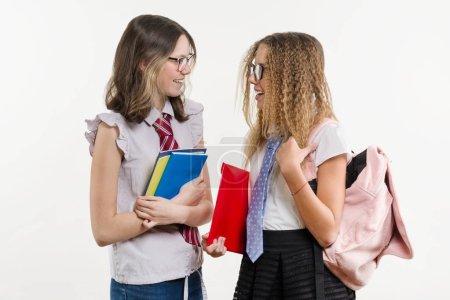 Photo pour Lycée heureux amis sont secret, de parler et d'adolescentes. Fond blanc, en uniforme, avec livres et Cahiers scolaires. - image libre de droit