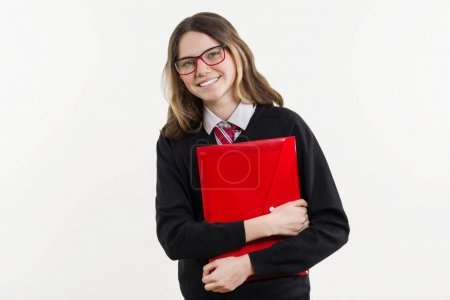 Photo for Girl teenager, high school student. Poses on a white background in school uniform and with textbooks in hands - Royalty Free Image