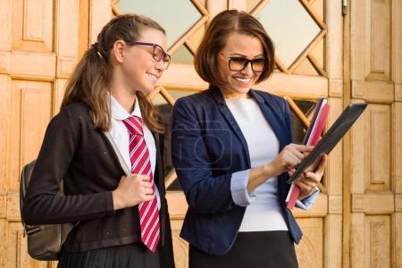 Photo pour Portrait d'un professeur de lycée avec une écolière près de la porte d'entrée de l'école en plein air - image libre de droit
