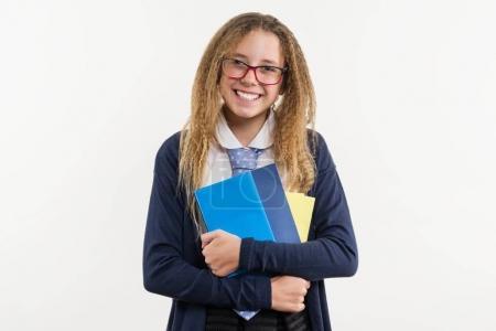 Foto de Adolescente chica, estudiante de secundaria. Posa sobre un fondo blanco uniforme escolar y libros de texto en las manos - Imagen libre de derechos