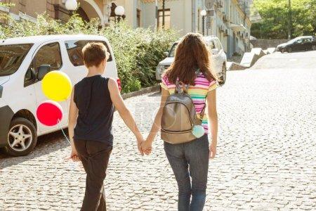 Photo pour Vue arrière ados main dans la main. Amitié, premier amour, Saint Valentin - image libre de droit