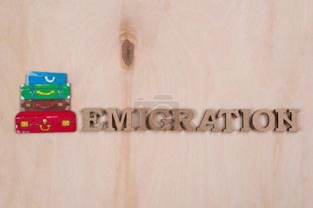 Photo pour Emmigration, le mot en lettres en bois abstraite. Surface en bois de fond et un tas de valises - image libre de droit