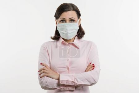 Photo for Business woman fears the virus and wears a face mask, white background - Royalty Free Image