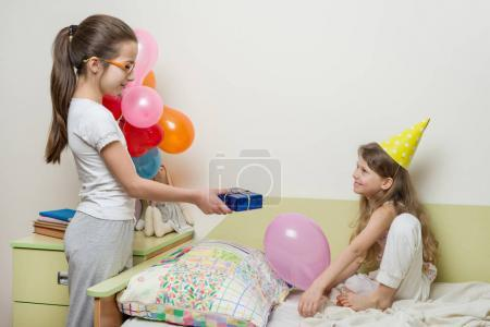 Photo for Birthday morning. Older sister giving surprise gift to her cute little sister. Children at home in bed. - Royalty Free Image