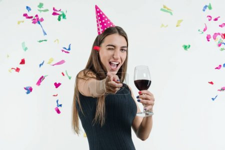Photo for Positive smiling woman at celebration party with a glass of wine and in a festival hat, Point your finger at you, Colored confetti flying on white background - Royalty Free Image