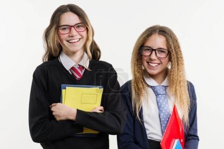 Foto de Retrato de primer plano de amigos feliz secundaria. Plantear en la cámara, en uniforme escolar, con libros y cuadernos, sobre un fondo blanco. - Imagen libre de derechos
