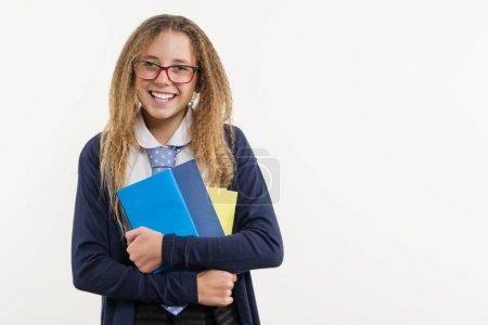 Foto de Adolescente chica, estudiante de secundaria. Posa sobre un fondo blanco en la escuela uniforme y con los libros de texto en las manos, espacio de copia. - Imagen libre de derechos